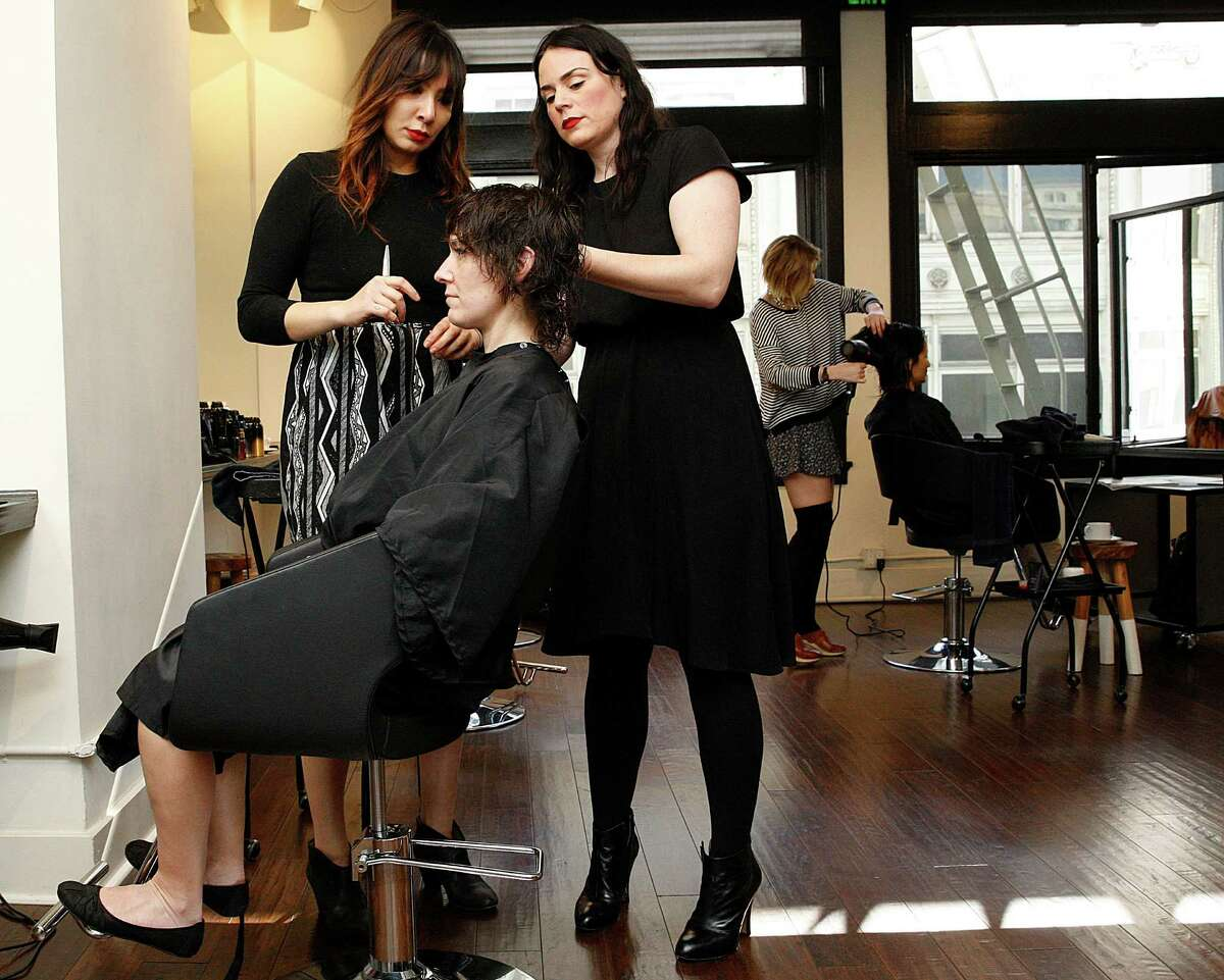 Michelle Snyder (middle, standing), owner of Barrow Salon in S.F., teaches cutting apprentice Jamie Chow (left) as she works on Simone Lee's hair.