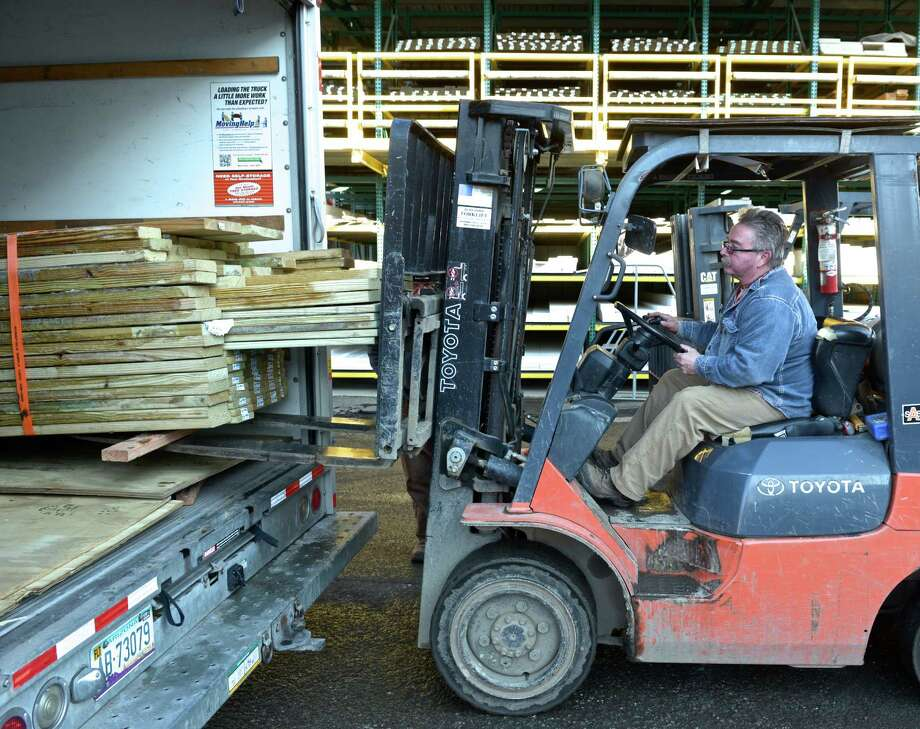 Bob Barber, left, guides a load of donated lumber into the back of a truck on Thursday, January 22, 2015. Dan Kelly, of Bethel, is using the donated lumber to build a playground at an orphanage in Haiti through his charity Tilt-A-World, the lumber was donated by a local supply company. Photo: H John Voorhees III / The News-Times
