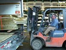Bob Barber, left, guides a load of donated lumber into the back of a truck on Thursday, January 22, 2015. Dan Kelly, of Bethel, is using the donated lumber to build a playground at an orphanage in Haiti through his charity Tilt-A-World, the lumber was donated by a local supply company.
