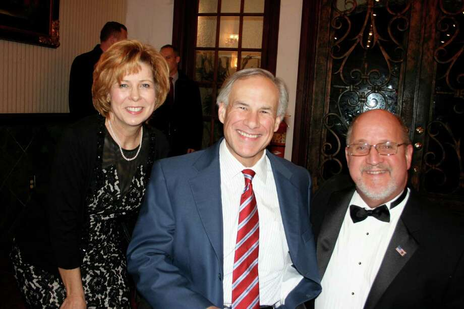 Fort Bend Republican County Chairman Mike Gibson, right, and his wife Tina, greeted Greg Abbott at the door of the Lincoln Reagan Dinner.  Abbott said in his talk that one of his primary objectives was to reduce state fees and regulations, and to fund mobility  projects. Photo: Joan Vogan