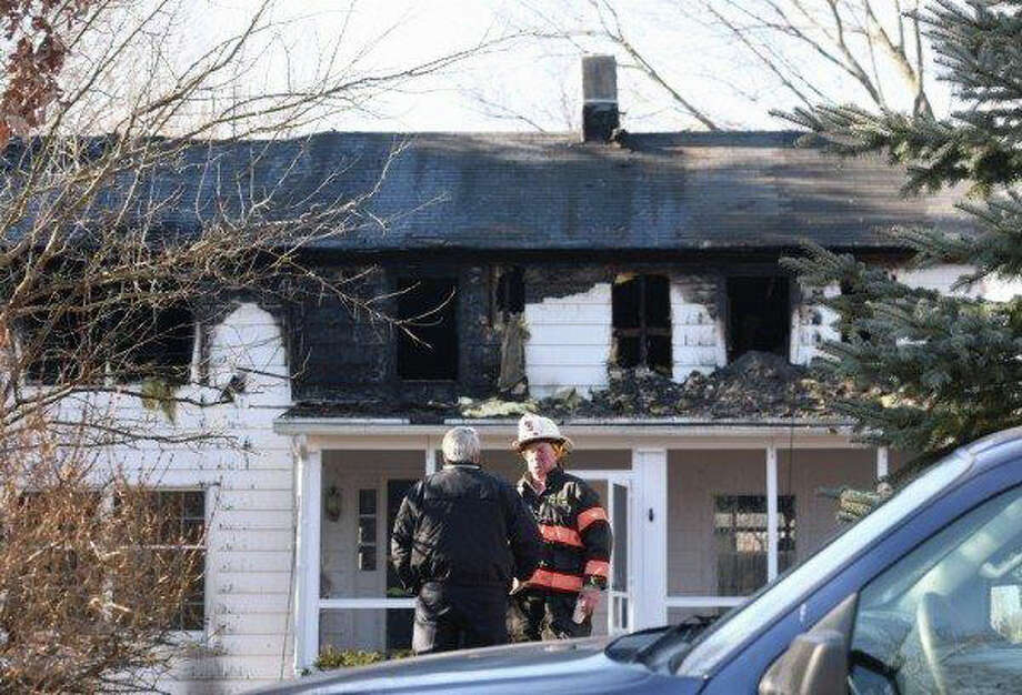 Greenwich firefighters respond to a 5:45 a.m. blaze at 178 Weaver Street in Greenwich after a neighbor was awakened early Friday by the bright light and 30 to 40 foot high flames. No one was injured, but the house sustained heavy damage. Photo: Anne W. Semmes, Paul Schott / Greenwich Time