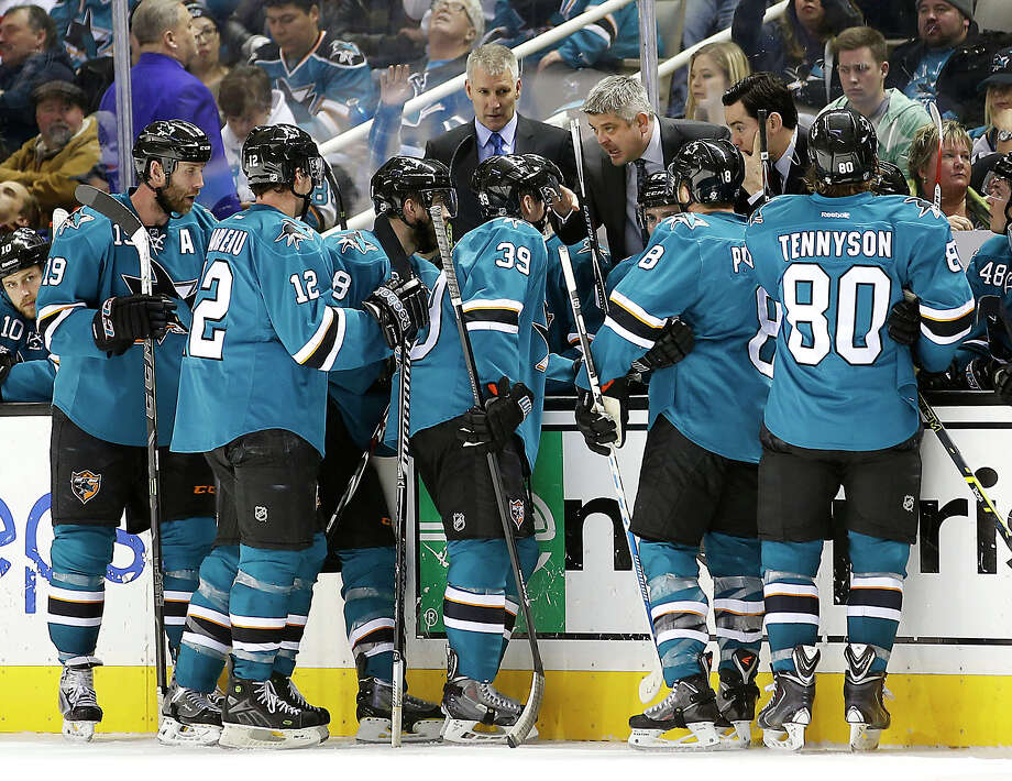 Todd McLellan (center) has seen some rough times for his team, but has the Sharks in playoff position at the break. Photo: TONY AVELAR / Associated Press / FR155217 AP