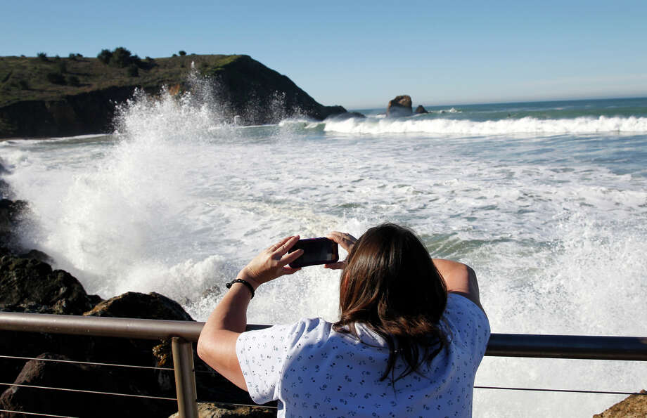 Cindy Meyer snaps photos of waves crashing onto the coast in Pacifica. Photo: Paul Chinn / The Chronicle / ONLINE_YES