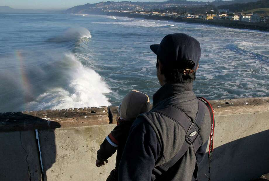 Percy Bautista watches the surf with his 1-year-old son Ezra from the municipal pier in Pacifica, Calif. on Friday, Jan. 23, 2015. The National Weather Service has issued a high surf advisory from the Sonoma County coastline south to Big Sur. Photo: Paul Chinn / The Chronicle / ONLINE_YES