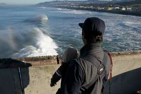 Percy Bautista watches the surf with his 1-year-old son Ezra from the municipal pier in Pacifica, Calif. on Friday, Jan. 23, 2015. The National Weather Service has issued a high surf advisory from the Sonoma County coastline south to Big Sur.