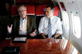 FILE - In this Oct. 31, 2012 file photo, then-Republican presidential candidate, former Massachusetts Gov. Mitt Romney talks with former Florida Gov. Jeb Bush as they fly on his campaign plane to Miami Fla. Outlining his possible rationale for a third presidential bid, Mitt Romney said Wednesday night that political leaders in both parties are failing to address the nation's most pressing problems _ climate change, poverty and education reform, among them _ as he acknowledged lessons learned from his failed 2012 presidential campaign. It came hours before he was scheduled to meet privately with Bush, whose aggressive steps toward a White House bid of his own helped force Romney's hand. Should they both run, they would compete for much of same establishment support.  (AP Photo/Charles Dharapak, File)