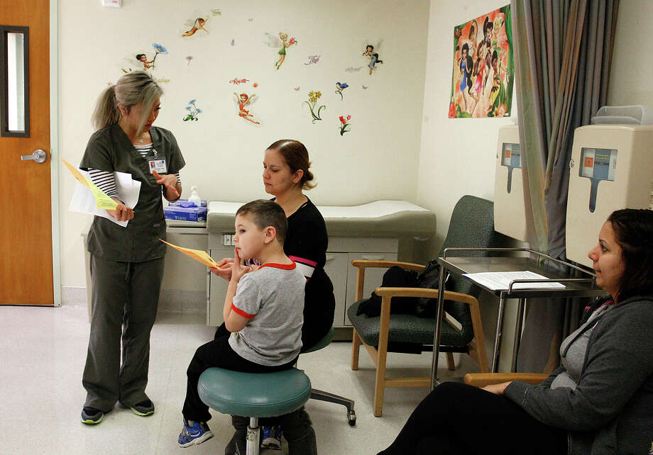Nurse Anna Quan Tong (left) prepares Damian Anguiano, 4, with his mom, Elsa Sandoval- Anguiano, for his measles vaccine at Kaiser in Redwood City, as Karla Sandoval watches. Photo: Liz Hafalia / The Chronicle / ONLINE_YES
