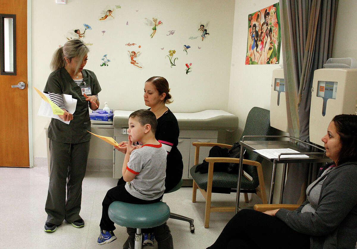 Nurse Anna Quan Tong (left) prepares Damian Anguiano, 4, with his mom, Elsa Sandoval- Anguiano, for his measles vaccine at Kaiser in Redwood City, as Karla Sandoval watches.