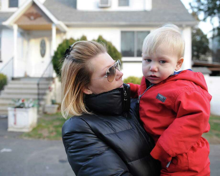 Dawn Fortunato holds her 2-year-old son, Charlie, outside their home near Armstrong Court in the Chickahominy section of Greenwich, Conn. Friday, Jan. 23, 2015.  Fortunato believes that there are environmental hazards in her neighborhood, which lies downstream from a former incinerator, that caused her son, Charlie, to get lead poisoning. Photo: Tyler Sizemore / Greenwich Time