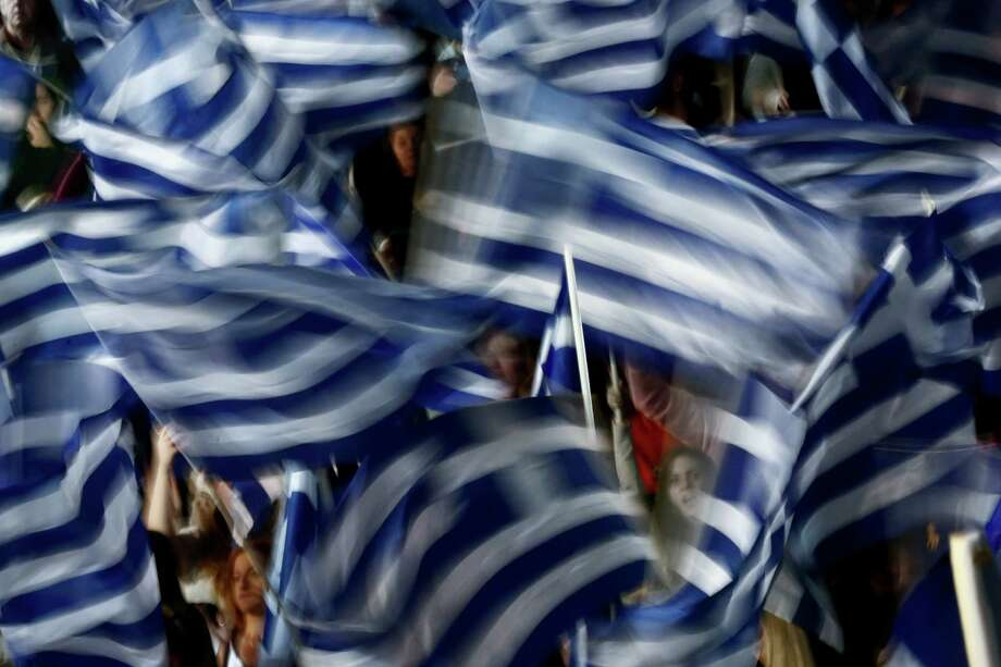 Supporters of Greece's Prime Minister Antonis Samaras wave Greek flags during his final campaign speech at the Taekwondo Indoor Stadium in southern Athens on Friday, Jan. 23, 2015. All opinion polls on Sunday's closely-watched national election agree: The radical left opposition Syriza party, which has vowed to rewrite the terms of Greece's international bailout, enjoys a lead of at least 4 percentage points over Prime Minister Antonis Samaras' conservatives. (AP Photo/Petros Giannakouris) Photo: Petros Giannakouris, STF / AP