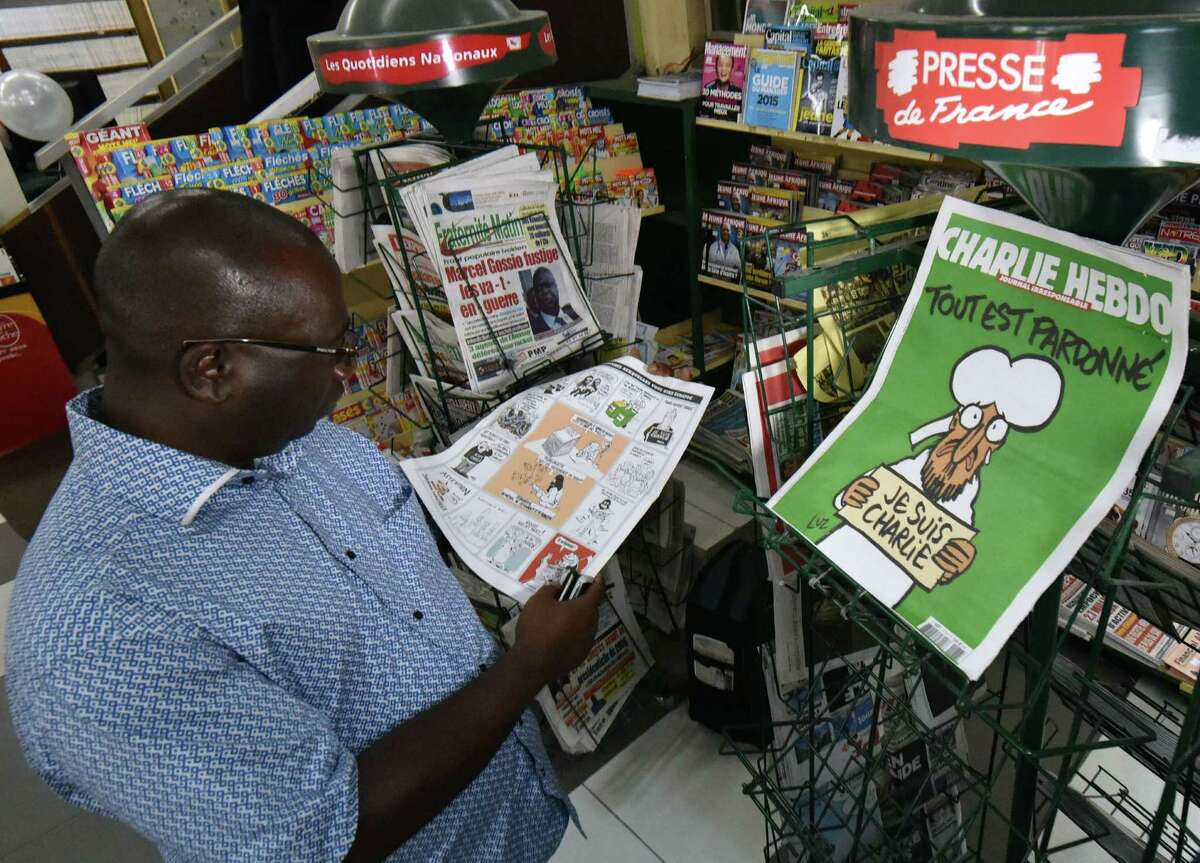 A man looks at the latest issue of French weekly newspaper Charlie Hebdo bearing a cartoon of Prophet Mohammed at a French bookseller in Abidjan. A reader comments on a photograph of the magazine and the image that ran in the E-N.