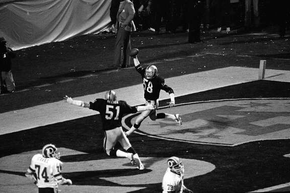 Los Angeles Raiders Jack Squirek (58) holds the ball aloft in the end zone after intercepting a pass by Washington Redskins quarterback Joe Theismann. Squirek scored a touchdown during second quarter action in Super Bowl XVIII in Tampa Stadium in Florida January 23, 1984, as teammate Bob Nelson (51) coming in to congratulate him (AP Photo)