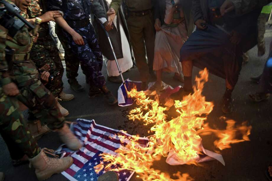 Yemeni protesters burn representations of American, French and Israeli flags during a demonstration to show their support for Houthi Shiite rebels in Sanaa, Yemen, Friday, Jan. 23, 2015. Thousands of protesters demonstrated Friday across Yemen, some supporting the Shiite rebels who seized the capital and others demanding the country's south secede after the nation's president and Cabinet resigned. (AP Photo/Hani Mohammed) Photo: Hani Mohammed, STR / AP