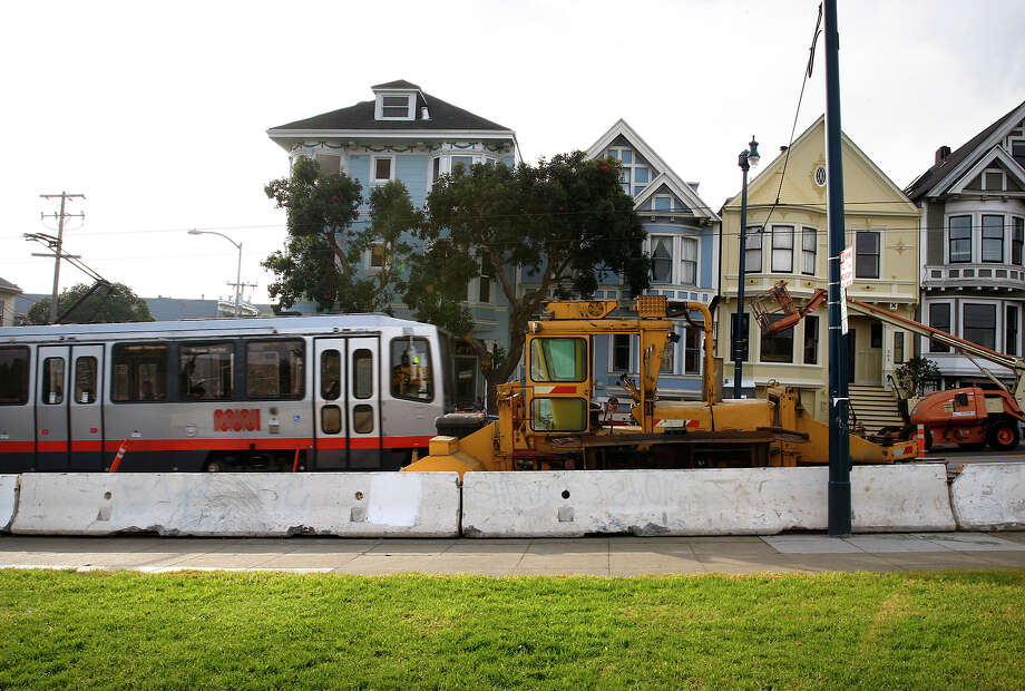 In this file photo, a Muni streetcar passes equipment in San Francisco's Duboce Park neighborhood being used in construction work going on inside the Sunset Tunnel. The work is designed to improve service on the busy N-Judah Metro line. Photo: Liz Hafalia / The Chronicle / ONLINE_YES