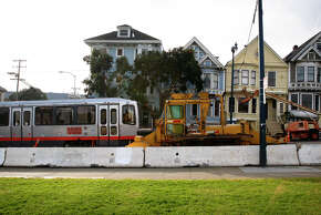 A Muni streetcar passes equipment in San Francisco's Duboce Park neighborhood being used in construction work going on inside the Sunset Tunnel. The work is designed to improve service on the busy N-Judah Metro line.