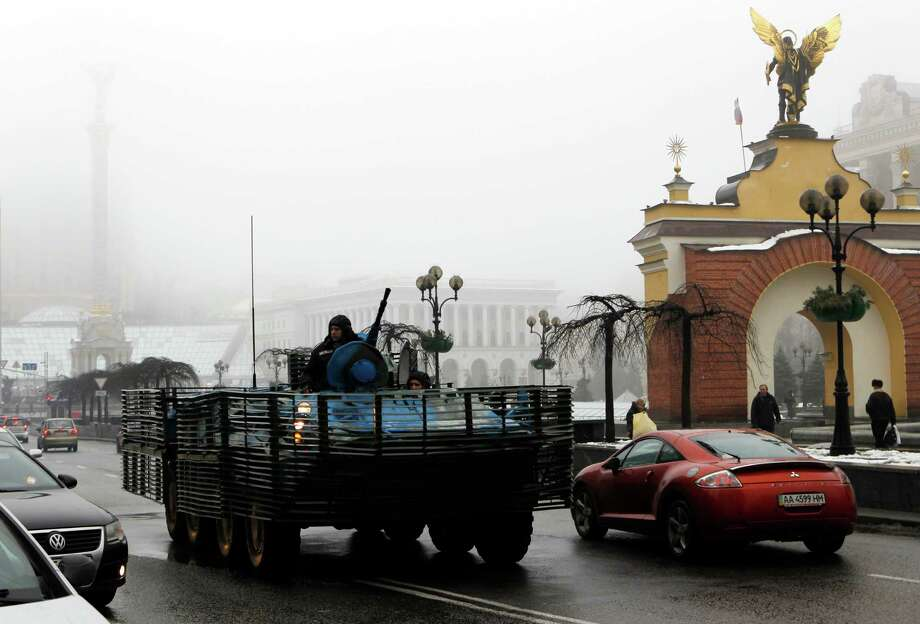 A Ukrainian military vehicle goes down the street on Independence Square in Kiev, Ukraine, Friday, Jan. 23, 2015.   Hours after a new peace initiative for Ukraine began taking shape, mortar shells rained down Thursday on the center of the main rebel-held city in the east, killing at least 13 people at a bus stop. (AP Photo/Sergei Chuzavkov) Photo: Sergei Chuzavkov, STF / AP