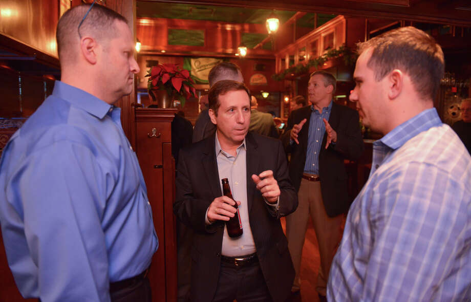 Joe Krull, (center) a member of the board of directors at the Denim Group, talks with David Neuman (left) and Mark Mangliclot, both of Ernst and Young, during a cybersecurity bootcamp reception recenty. Photo: Express-News File Photo / San Antonio Express-News