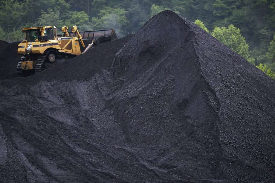 A bulldozer operates atop a coal mound in Shelbiana, Kentucky. Prices of thermal coal and metallurgical coal have tumbled more than half since 2011 on supply additions and slowing demand in China, the biggest commodities consumer. With OPEC insistent that it won't curb crude output, and U.S. production rising at its fastest weekly pace in more than 30 years, oil markets may be in line for similar prolonged pain. Photo: Luke Sharrett /Getty Images / 2014 Getty Images