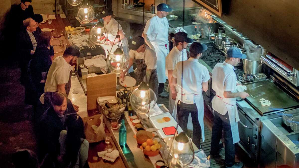 The long narrow kitchen at Cockscomb in S.F. is the focal point of the restaurant, where a cadre of white-coated chefs, including owner Chris Cosentino, prepare the food.