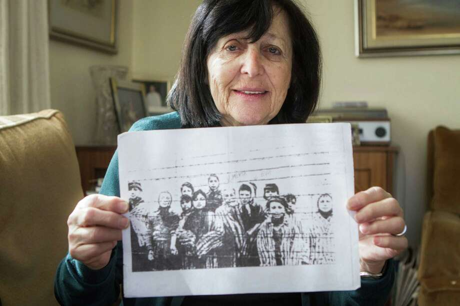 In this photo taken Thursday, Jan. 22, 2015, Marta Wise holds a famous black-and-white photo, taken by the Russian liberators of Auschwitz, showing her, center, with about a dozen children in rags standing behind a row of barbed wire that has become one of the most iconic images of the Holocaust, as she poses for a portrait in her house in Jerusalem. Wise was ill and emaciated when she heard the distant sound the soldiers marching toward Auschwitz. The 10-year-old Slovakian Jew assumed it was German troops coming to get her but once she saw the red stars on their uniforms she realized they were Russian. Her nightmare was over. She was liberated. (AP Photo/Dan Balilty) Photo: Dan Balilty, STR / AP
