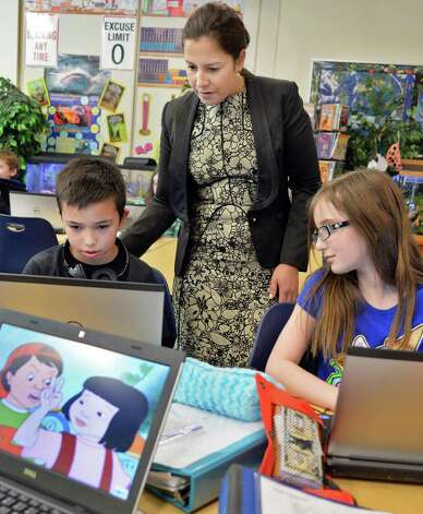 Congresswoman Elise Stefanik, a member of the House Committee on Education and the Workforce, looks over the work of 5th graders Gino Rubertis, left, and Avery Scatena during a tour of Gordon Creek Elementary School Friday Jan. 23, 2015, in Ballston Spa, NY.   (John Carl D'Annibale / Times Union) Photo: John Carl D'Annibale / 00030322A