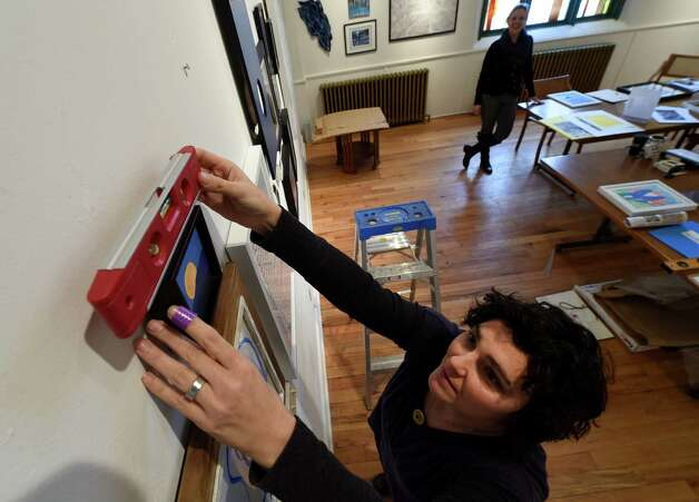 Belinda Colon, exhibits manager levels a piece of art for the Spring Street Gallery show Wednesday afternoon Jan. 21, 2015 in Saratoga Springs, N.Y.      (Skip Dickstein/Times Union) Photo: SKIP DICKSTEIN / 00030296A