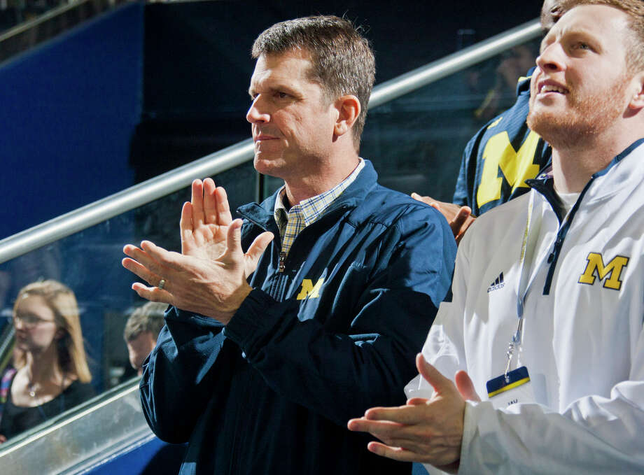 Michigan head football coach Jim Harbaugh sits with son Jay at a Wolverines home basketball game. Photo: Tony Ding / Associated Press / FR143848 AP