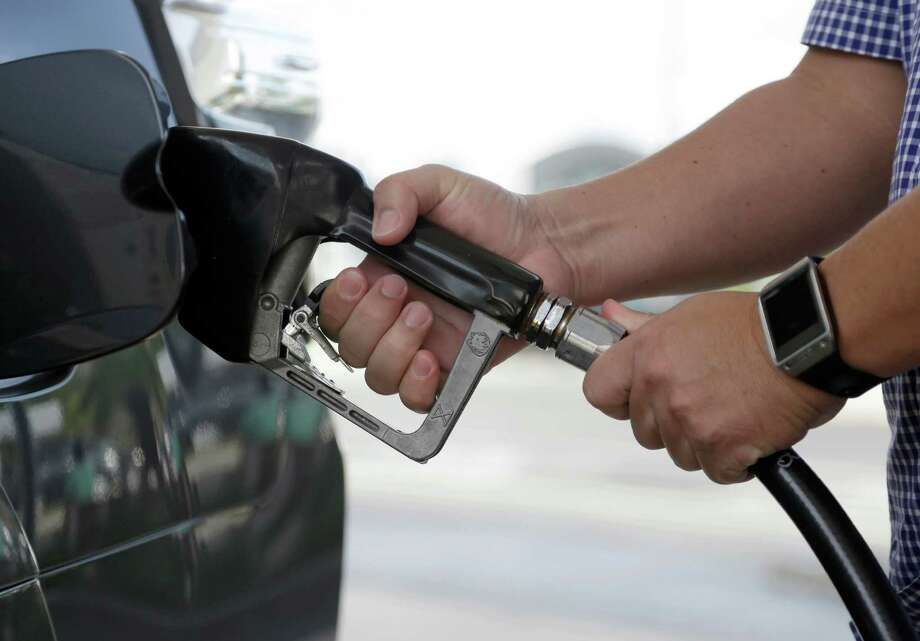 A motorist puts fuel in his vehicle Friday in Miami. For the first time since 2009, most Americans are paying less than $2 a gallon. Photo: Lynne Sladky /Associated Press / AP