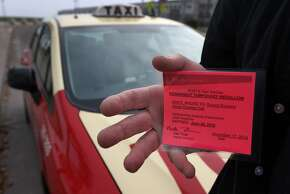 Cab driver Gerard Rowland displays his permanent temporary taxi medallion in San Francisco, Calif. on Friday, Jan. 16, 2015. A cab driver for over 20 years, Rowland scored last November when the opportunity came up to purchase his own coveted taxi medallion and he jumped at the chance.