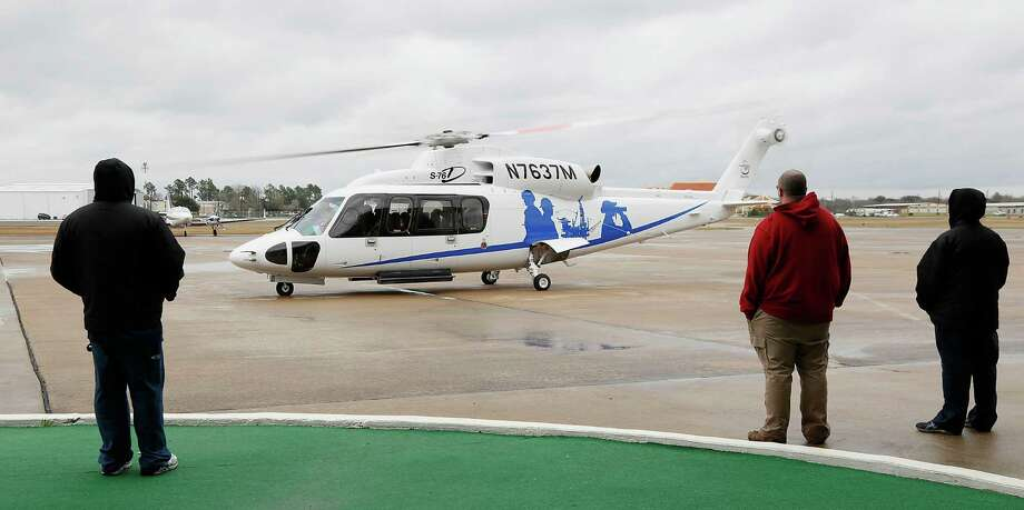 Grounds crew members look on as a Sikorsky model S-76D helicopter prepares to taxi during a demonstration Friday for offshore oil and gas company representatives. ( James Nielsen / Houston Chronicle ) Photo: James Nielsen, Staff / © 2015  Houston Chronicle