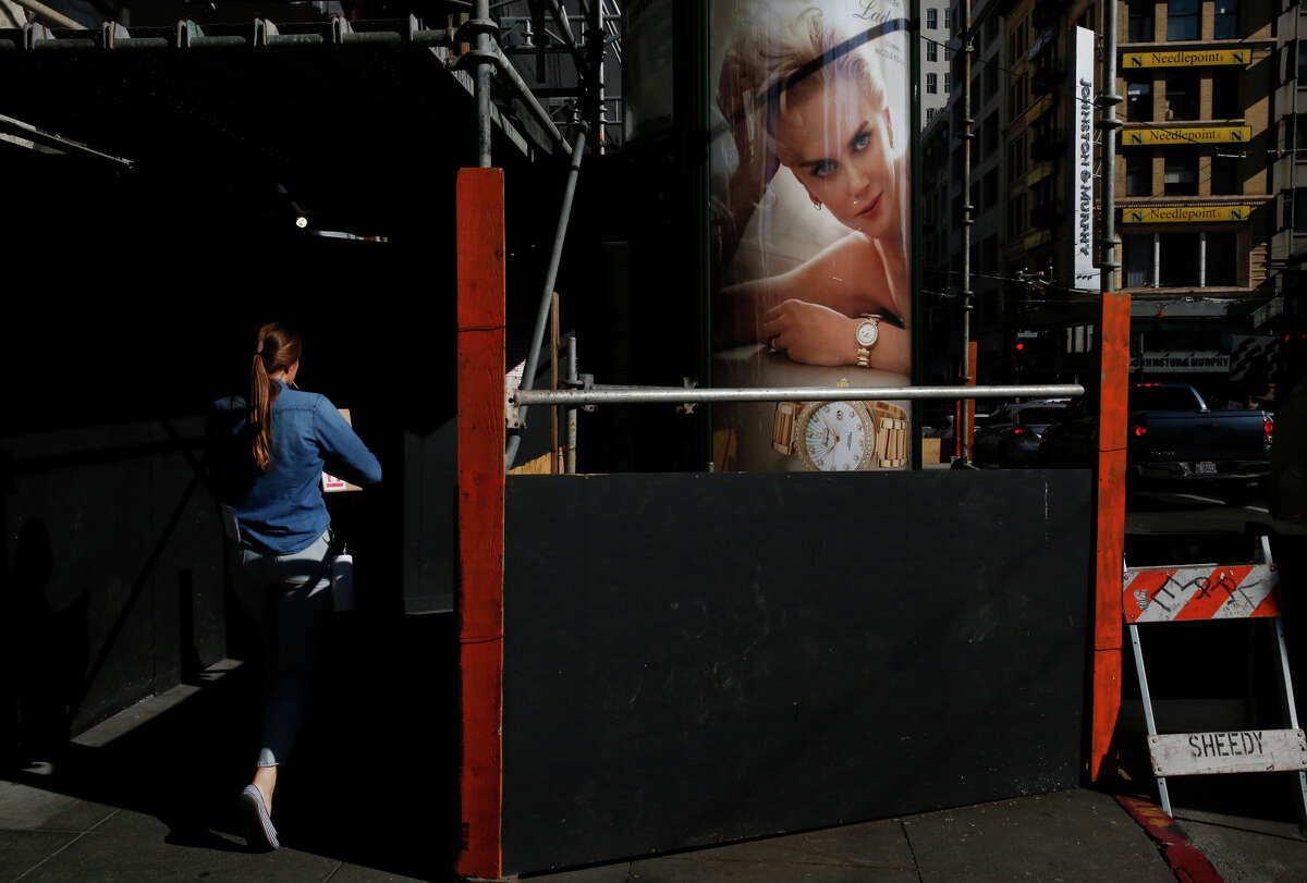 A pedestrian walks past an ad for a luxury watch near Union Square in increasingly wealthy San Francisco.