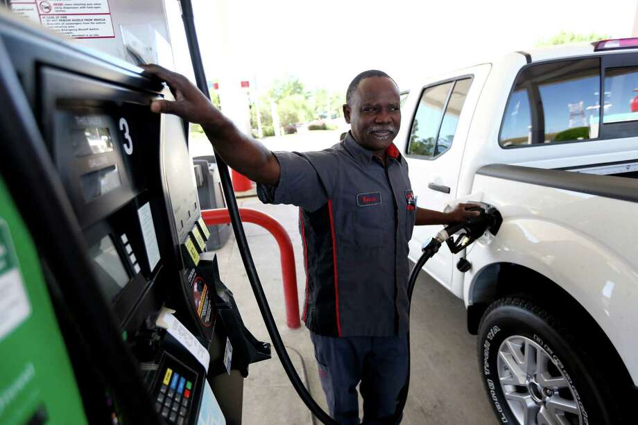 Ronnie Miller fills up at the Conoco at 700 North Dairy Ashford. Miller says prices should be even lower, although some prices have fallen under $2 a gallon. Photo: Gary Coronado, Staff / © 2014 Houston Chronicle