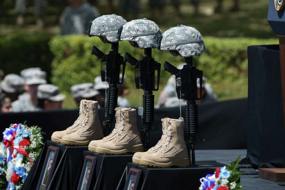 A tribute to three slain soldiers stands in front of a lectern before an April 9 memorial service at Fort Hood. Photo: Doug Mills /New York Times / NYTNS