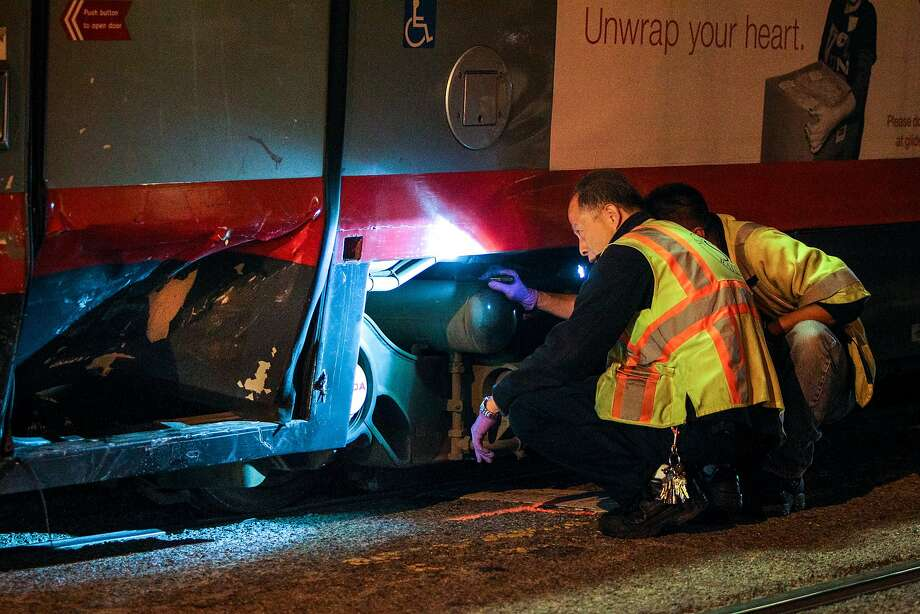 SFMTA officials investigate an L-Taraval Muni train which was hit by a car at the corner of 19th Avenue and Ulloa Street, Friday, Jan. 23, 2015, in San Francisco, Calif. Photo: Santiago Mejia, The Chronicle