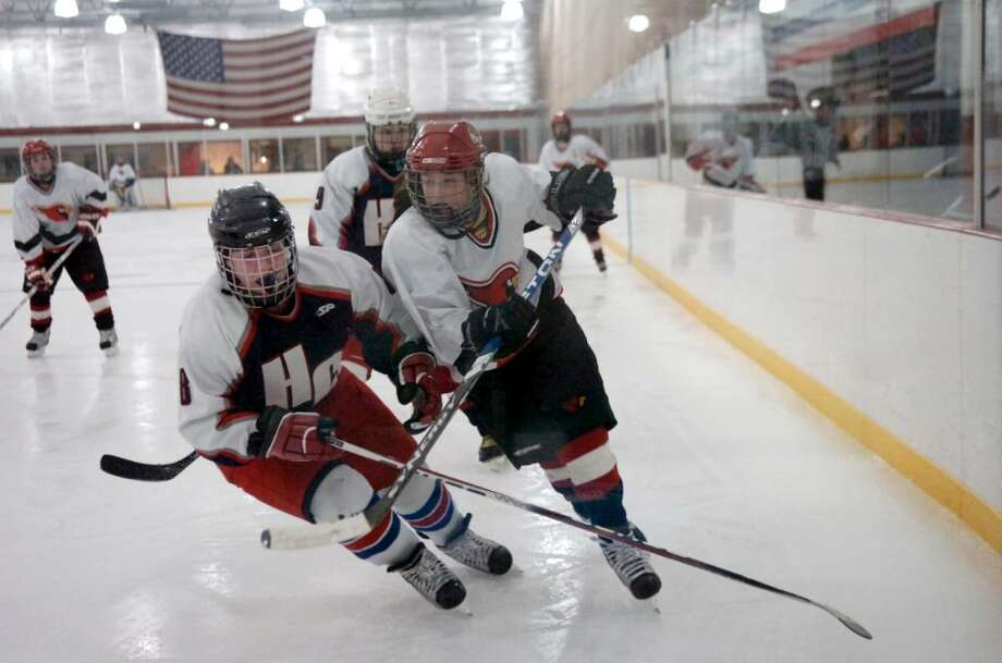 Conard-Hall's Cassie Festa,(#8), left and Greenwich High School's Hannah Jeffery (#13) fight for the puck in the girls hockey state playoffs at Dorothy Hamill Skating Rink, on Monday, March 1, 2010. Photo: Helen Neafsey / Greenwich Time
