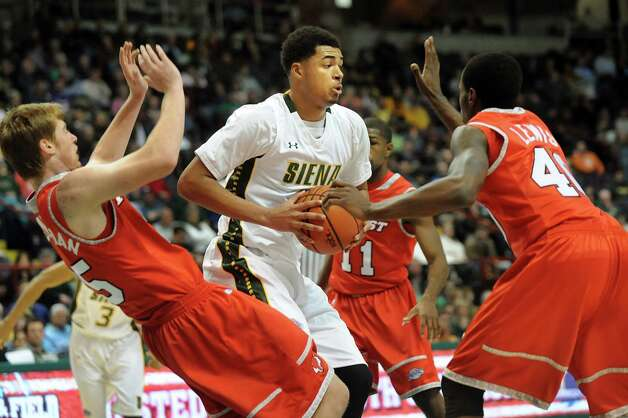 Siena's Javion Ogunyemi, center, takes control of the ball as Marist's Connor McClenaghan left, and Chavaughn Lewis defend during their basketball game on Friday, Jan. 23, 2015, at Times Union Center in Albany, N.Y. (Cindy Schultz / Times Union) Photo: Cindy Schultz / 00030241A