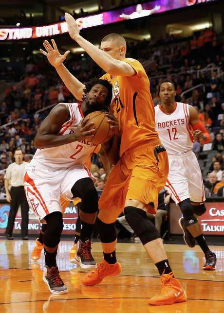 Rockets point guard Pat Beverley is challenged by the Suns' Alex Len as he drives to the basket during Friday's win at Phoenix. Beverley had 14 points. Photo: Christian Petersen, Staff / 2015 Getty Images
