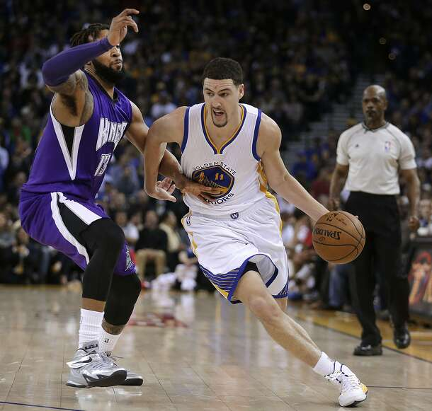 Golden State Warriors' Klay Thompson drives the ball around Sacramento Kings' Derrick Williams (13) during the third quarter of an NBA basketball game  Friday, Jan. 23, 2015, in Oakland, Calif. (AP Photo/Ben Margot)