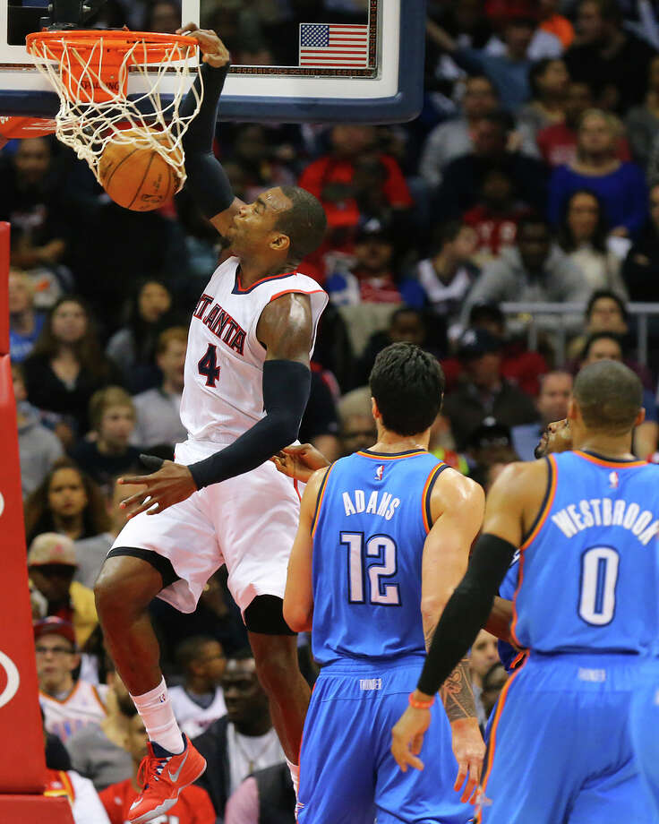 Hawks forward Paul Millsap gets past Thunder defenders Steven Adams (12) and Russell Westbrook (0) for a dunk Photo: Curtis Compton / McClatchy-Tribune News Service / Atlanta Journal-Constitution