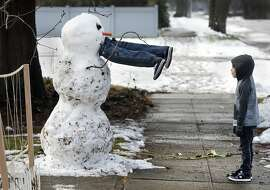 Miles McQuesten, 5, stands in front of a snowman, Friday, Jan. 23, 2015, in Spokane, Wash.  The boy and his father, Rick, built the snowman Friday morning, and the legs are constructed from branches and newspapers.