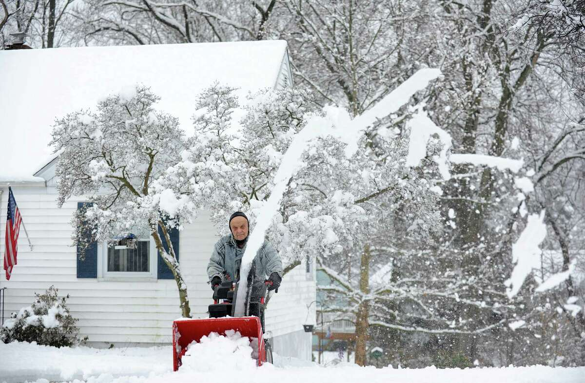 Ed Petitti clears the snow from his driveway on Reid St. in Fairfield, Conn. on Saturday, Jan. 24, 2015. After an overnight accumulation, the snow transitioned to rain by late morning.