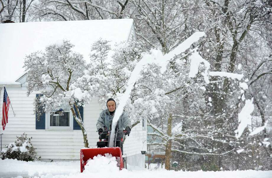 Ed Petitti clears the snow from his driveway on Reid St. in Fairfield, Conn. on Saturday, Jan. 24, 2015. After an overnight accumulation, the snow transitioned to rain by late morning. Photo: Cathy Zuraw / Connecticut Post