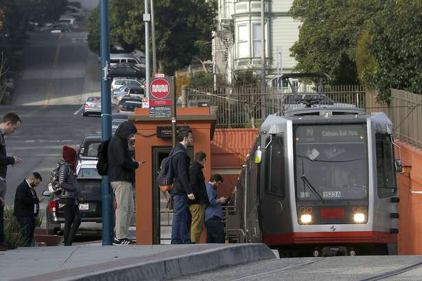 Commuters wait for the Muni streetcar next to the Sunset Tunnel on Duboce at Noe streets in San Francisco, Calif., on Thursday, January 22, 2015.  Work has already begun for the track in the tunnel for eastbound streetcars.  Neighbors living near Duboce Park, on the east end of Muni's Sunset Tunnel, are upset by the noise generated by the N-line-Sunset Tunnel trackway improvement project that takes place on weekends because SFMTA only authorizes construction starting 8pm on Friday night to 4am on Monday mornings.