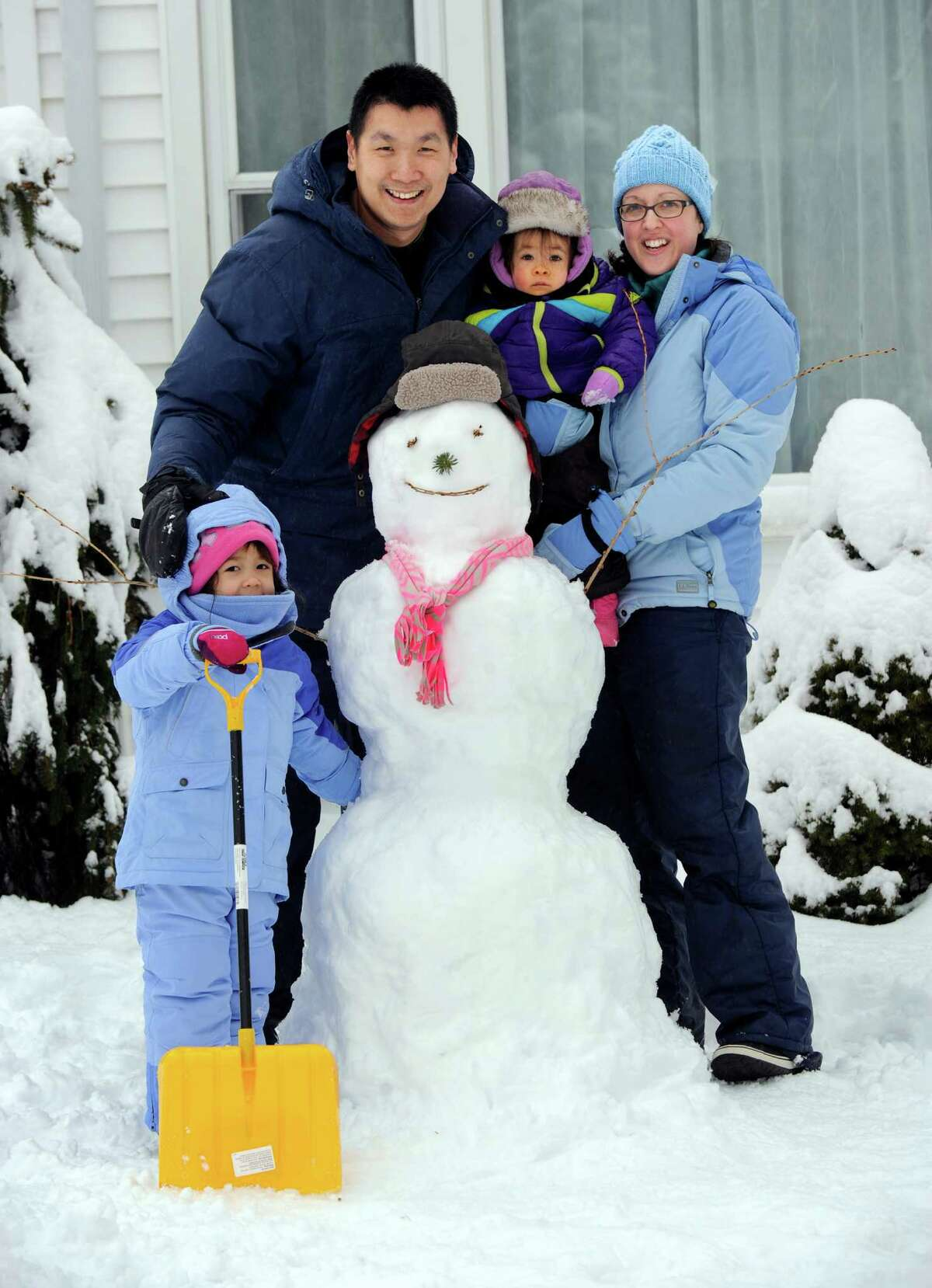 The Boediarto family of Brookfield, Conn,- parents Steven and Bree, with daughters, Senora, 3 1/2, left and Adelynn, 15-months-old, pose with the snowman they created after an overnight snowfall, Saturday morning, January 24, 2015.