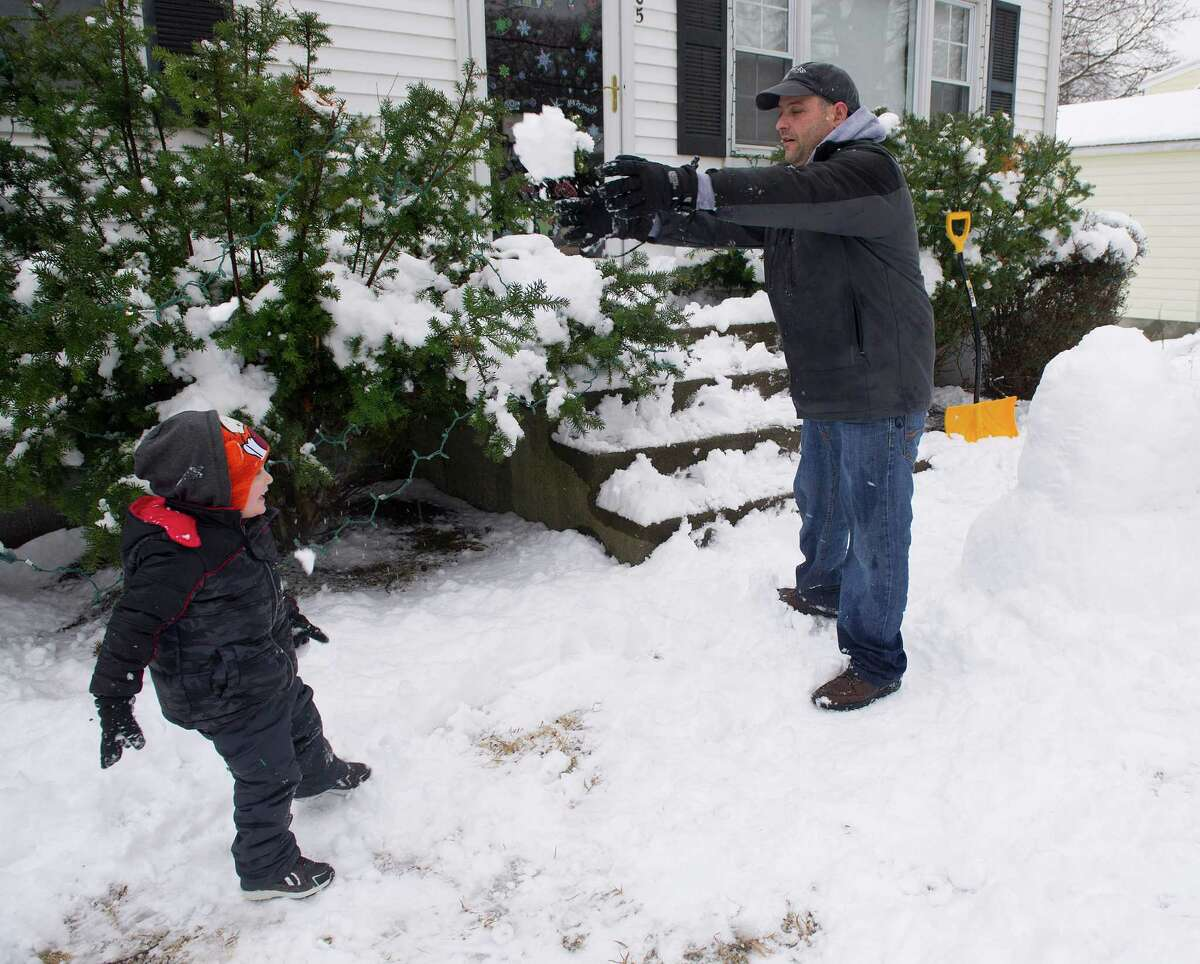 Masen Bardelli, 3, and his father, Joseph, take a break from building a snowman Masen named