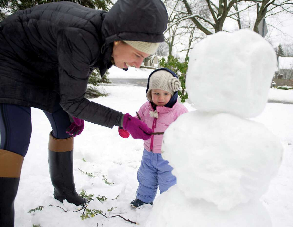 Josephine Schaefer, 1, watches as her mother, Arley, adds arms to their snowman in Stamford, Conn., on Saturday, January 24, 2015.