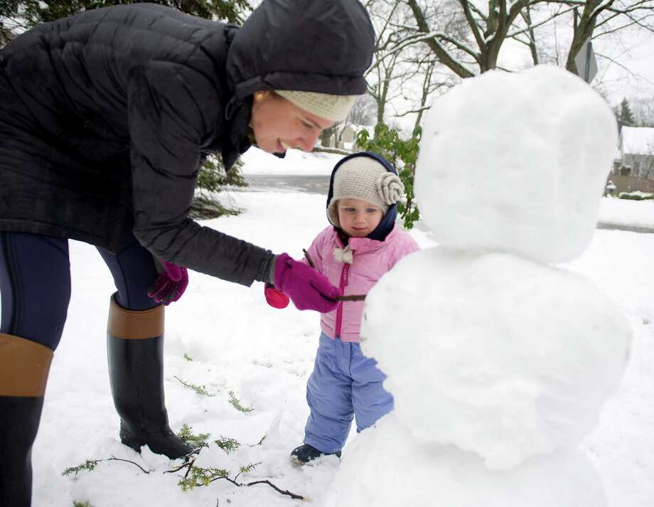 Josephine Schaefer, 1, watches as her mother, Arley, adds arms to their snowman in Stamford, Conn., on Saturday, January 24, 2015. Photo: Lindsay Perry / Stamford Advocate