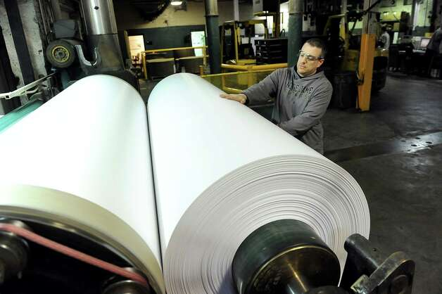 Employee Chris Kilmer checks a reel of paper to make sure it's spooling evenly on Wednesday, Jan. 21, 2015, at Mohawk  Paper in Cohoes, N.Y. (Cindy Schultz / Times Union) Photo: Cindy Schultz / 00030282A
