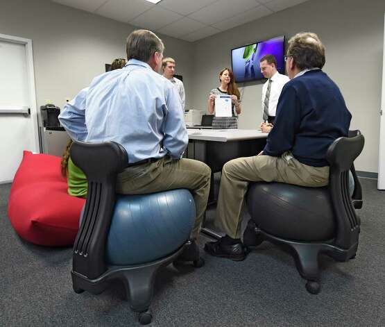 CEO Dawn Abbuhl, center, holds a staff meeting Thursday morning Jan. 22, 2015 at the Repeat Business Systems Co. in Colonie, N.Y.  Some of the staff sit on ball chairs and some sit on an oversized bean bag.   (Skip Dickstein/Times Union) Photo: SKIP DICKSTEIN / 00030286A