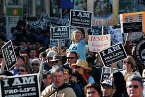 Top: Thousands of antiabortion demonstrators march along Market Street in S.F. Aside from vocal skirmishes with pro-choice protesters, things remained peaceful.